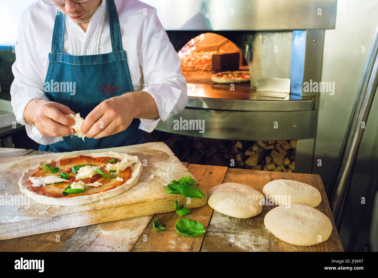 The chef fills the pizza with tomato sauce and mozzarella cheese then ready to be cooked in the wood oven Italy - Stock Image