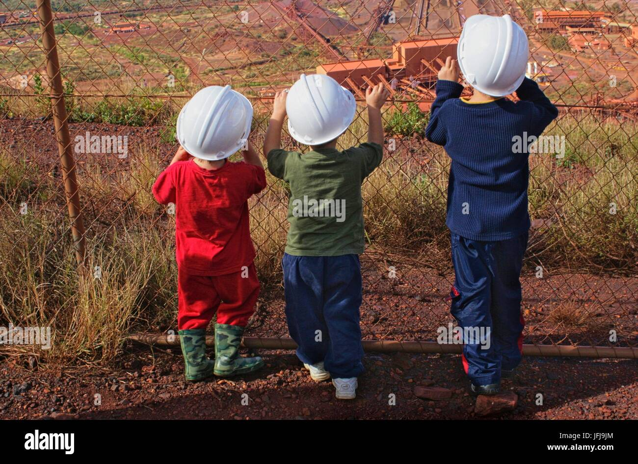 Three children wearing protective mining helmets looking