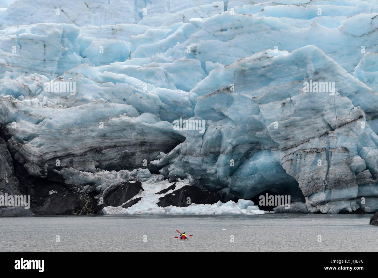 Red canoe (kayak) close to glacier front, Portage glacier, Alaska, USA - Stock Image