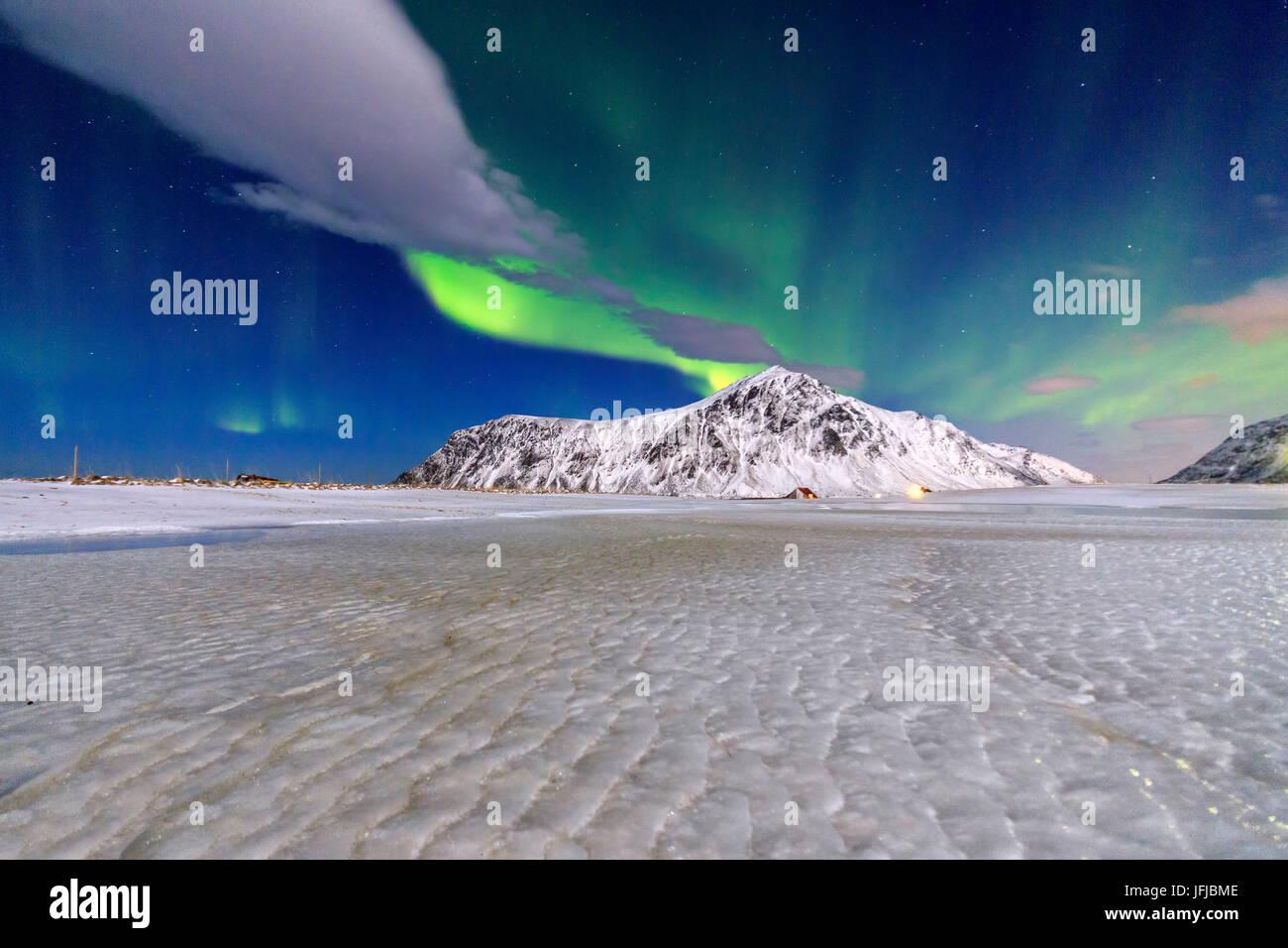 Northern Lights illuminate the sky and the snowy peaks, Flakstad, Lofoten Islands Northern Norway Europe - Stock Image
