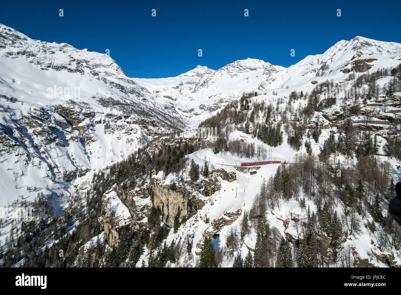 Aerial picture of the red Bernina train going to Bernina Pass in winter, Alp Grum, Poschiavo Valley, Canton Grigioni, - Stock Image