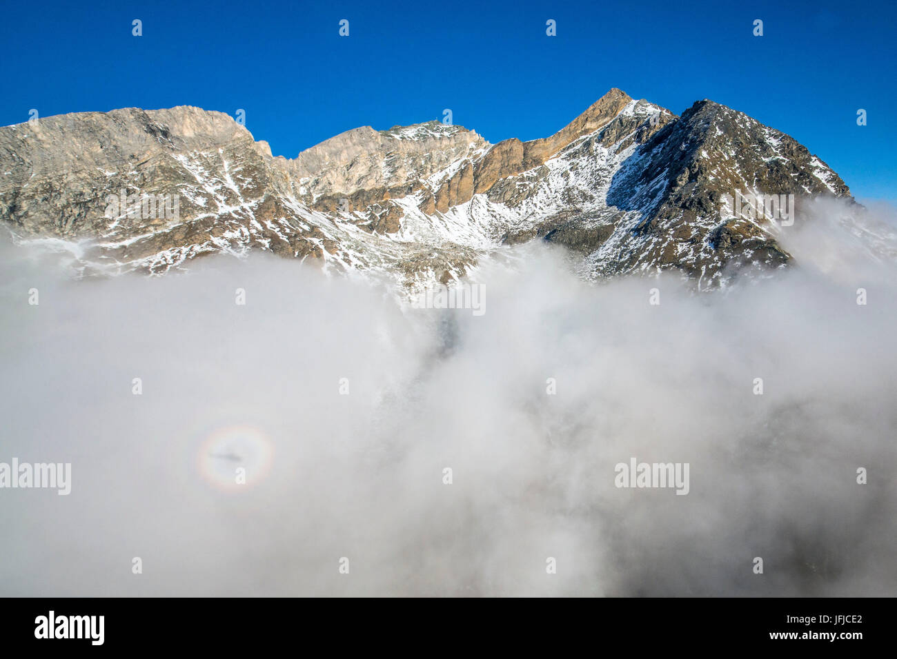 The humidity of clouds and the shadow of helicopter create Brocken spectre in Switzerland, Zermatt, Europe - Stock Image