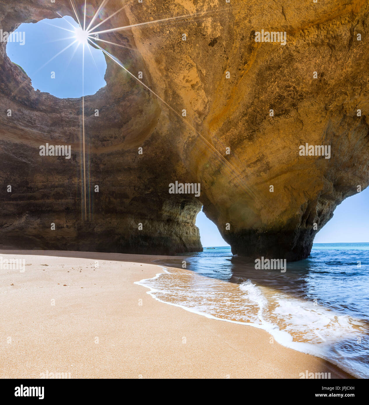 The sun shines through the natural rocky windows inside the caves of Benagil Faro District Algarve Portugal Europe - Stock Image