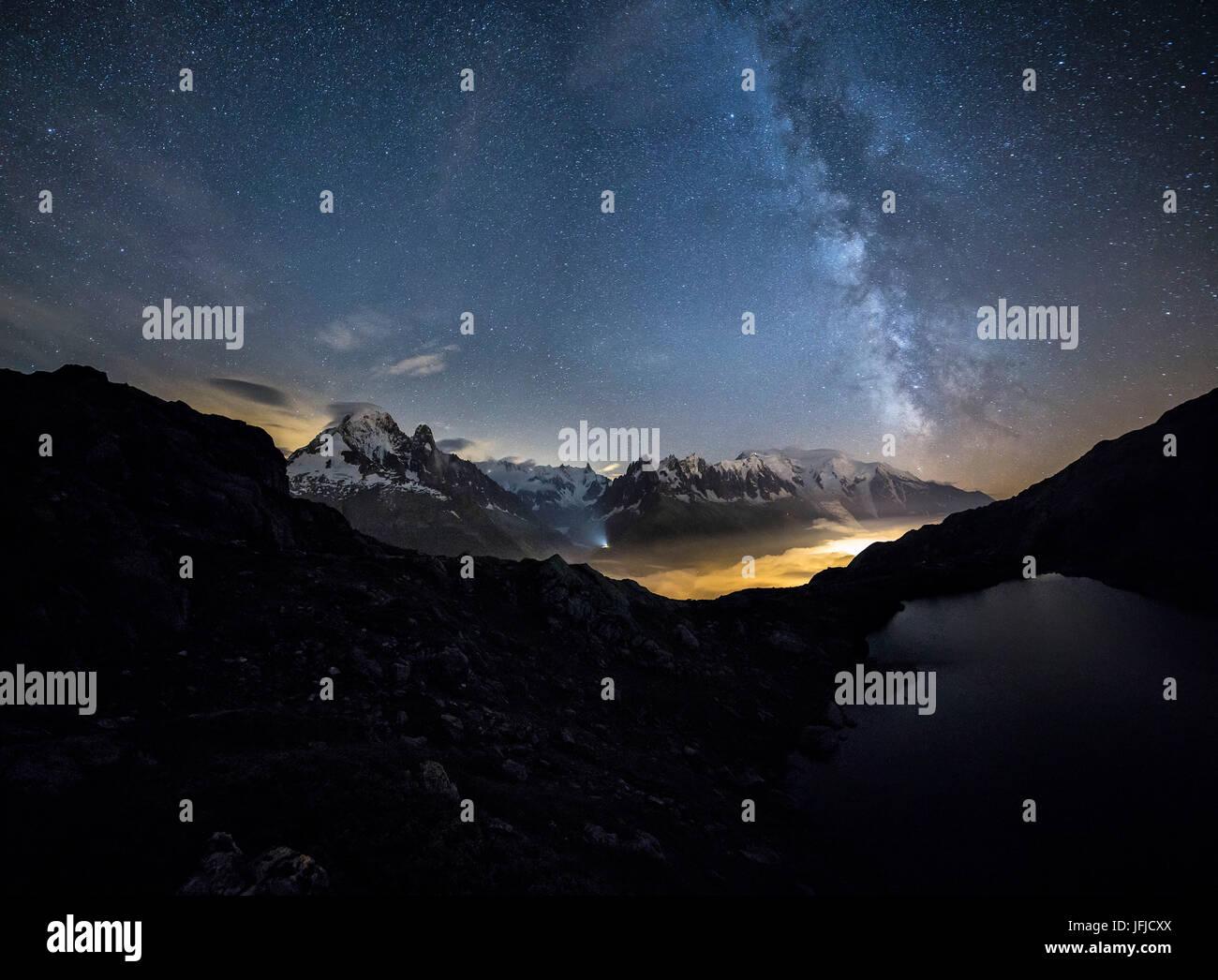 Stars and Milky Way illuminate the snowy peaks around Lac de Cheserys Chamonix Haute Savoie France Europe - Stock Image