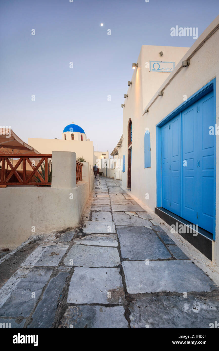 The moon above the white houses and blue domes of the churches in a narrow alley of Oia Santorini Cyclades Greece - Stock Image