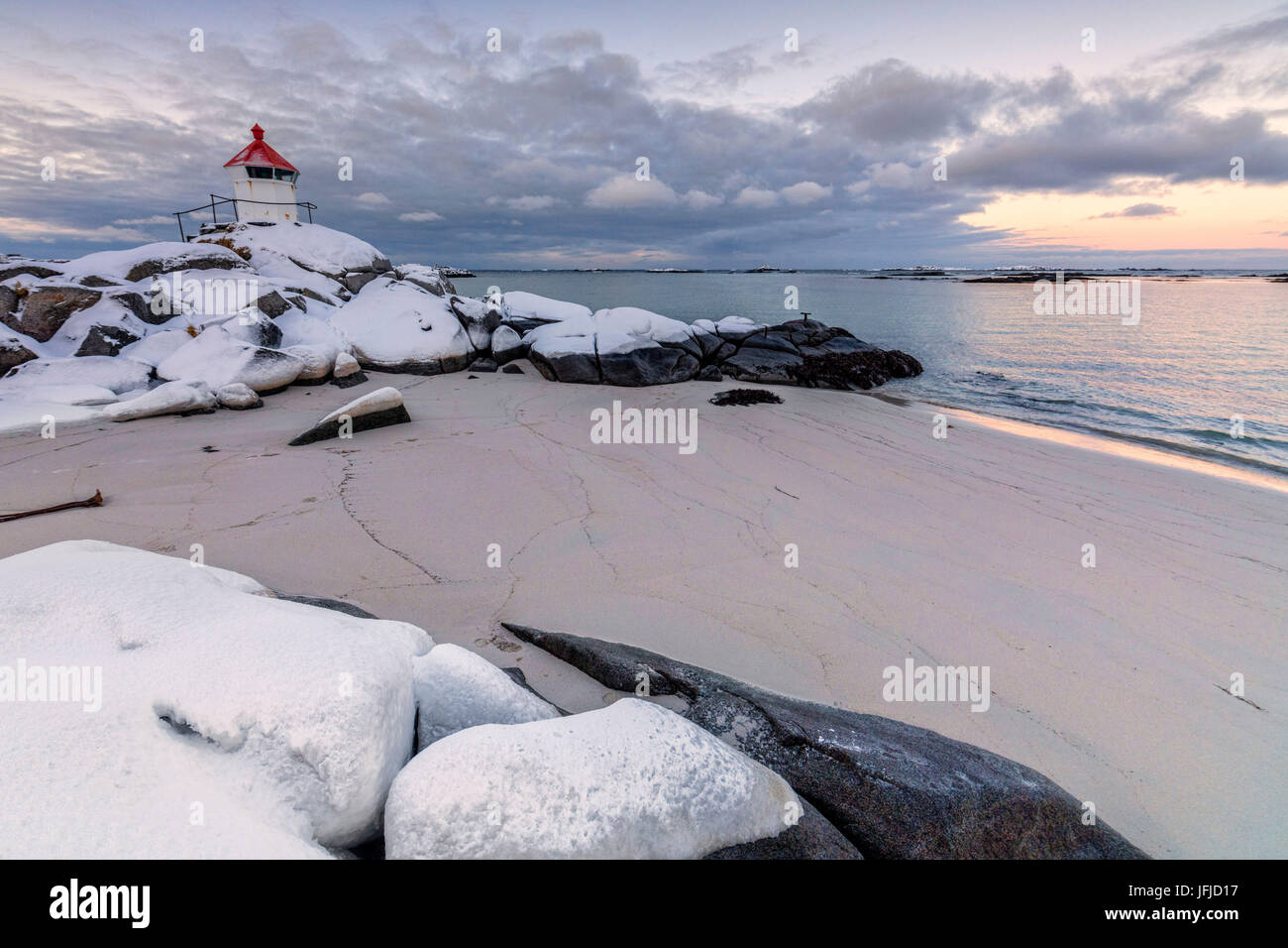 Colorful arctic sunset on the lighthouse surrounded by snow and icy sand Eggum Vestvagoy Island Lofoten Islands Stock Photo