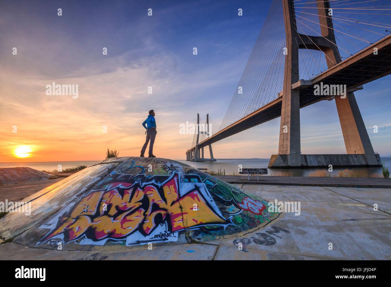 A tourist admires the majestic Vasco da Gama Bridge over the River Tagus Parque das Nações Lisbon Portugal Europe Stock Photo
