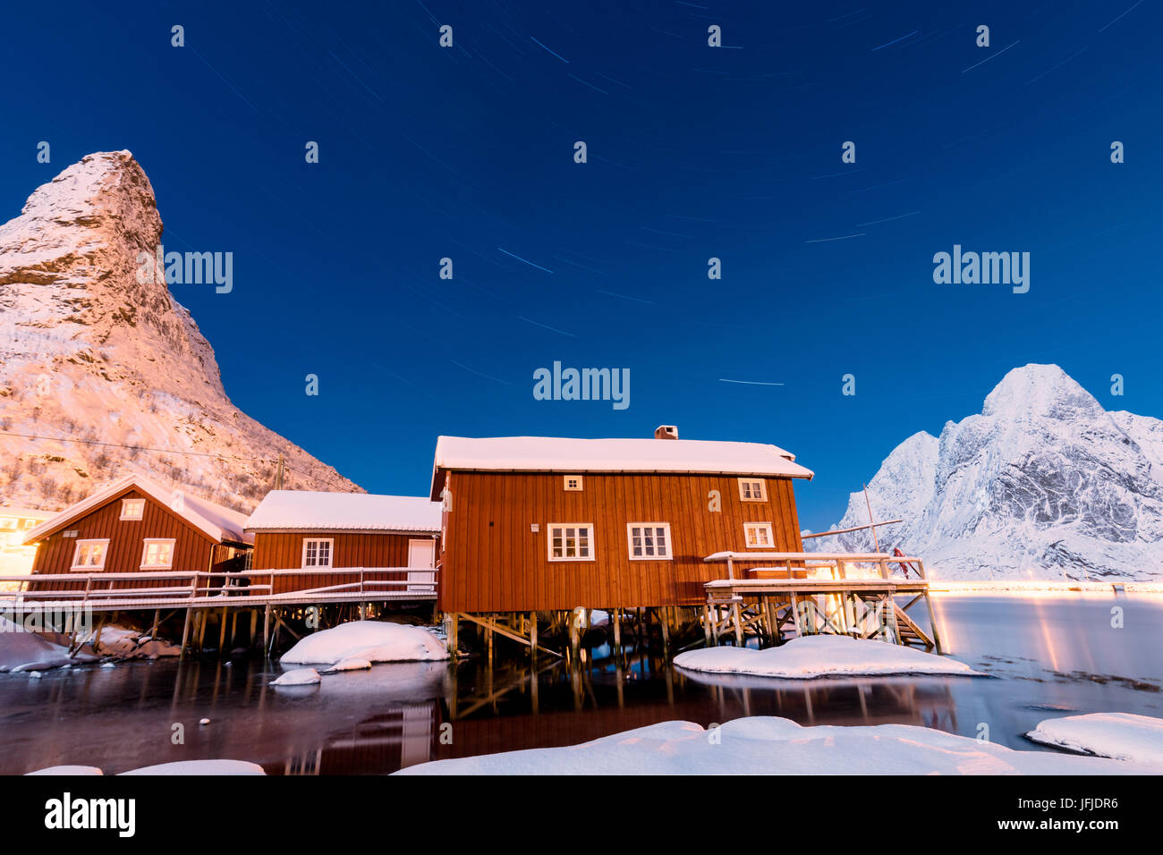Starry night on the snowy peaks surrounded by the frozen sea and fishermen houses Reinevagen Bay Lofoten Islands - Stock Image