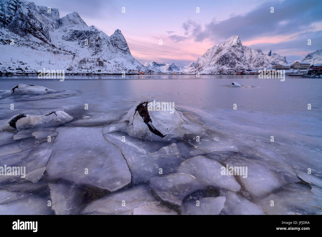The pink colors of sunset and the frozen sea surround the fishing villages Reine Nordland Lofoten Islands Norway - Stock Image