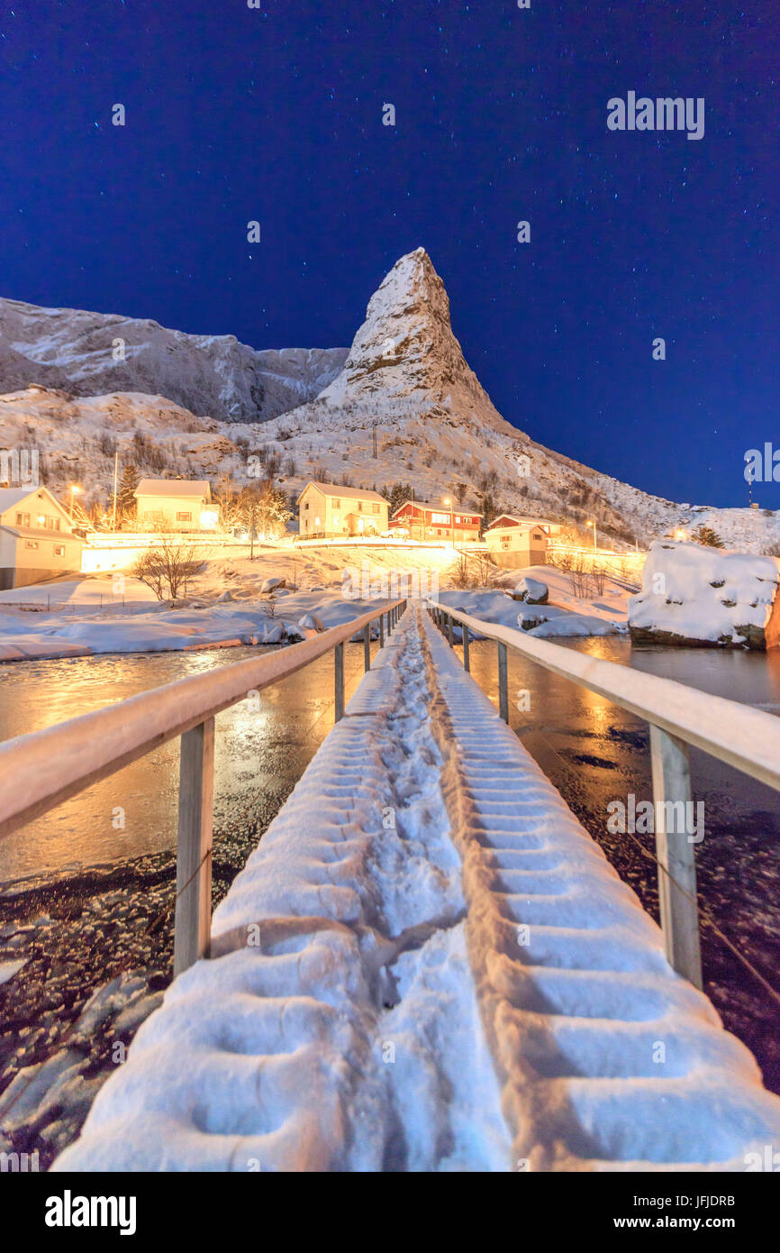 Starry night on the snowy peaks surrounded by the frozen sea Reinevagen Bay Nordland Lofoten Islands Norway Europe - Stock Image