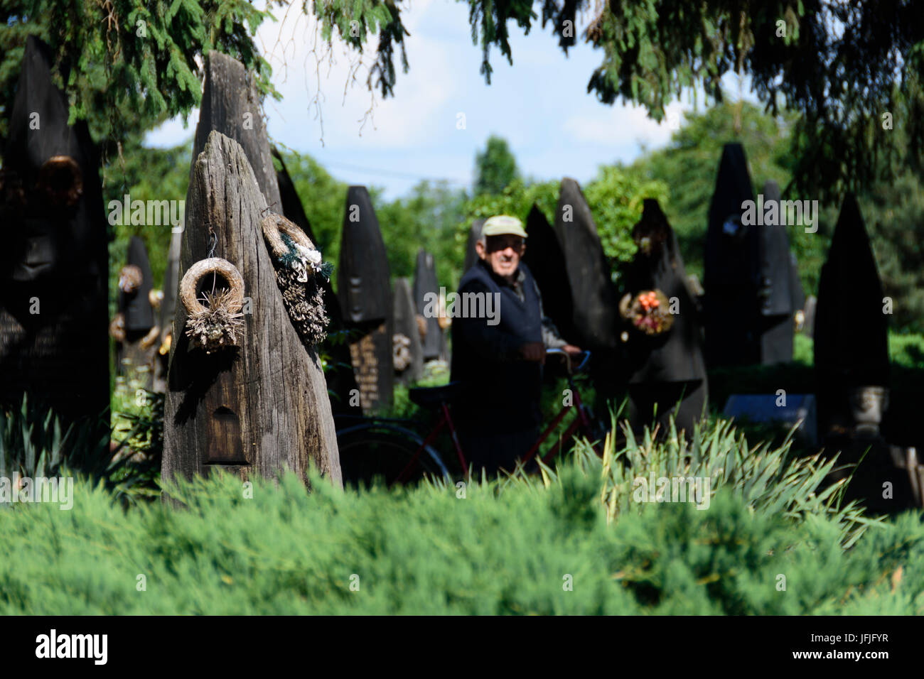 Szatmarczeke , Hungary. Wooden boat shaped gravestones on the cemetery. And old visitor with a bicycle. Stock Photo