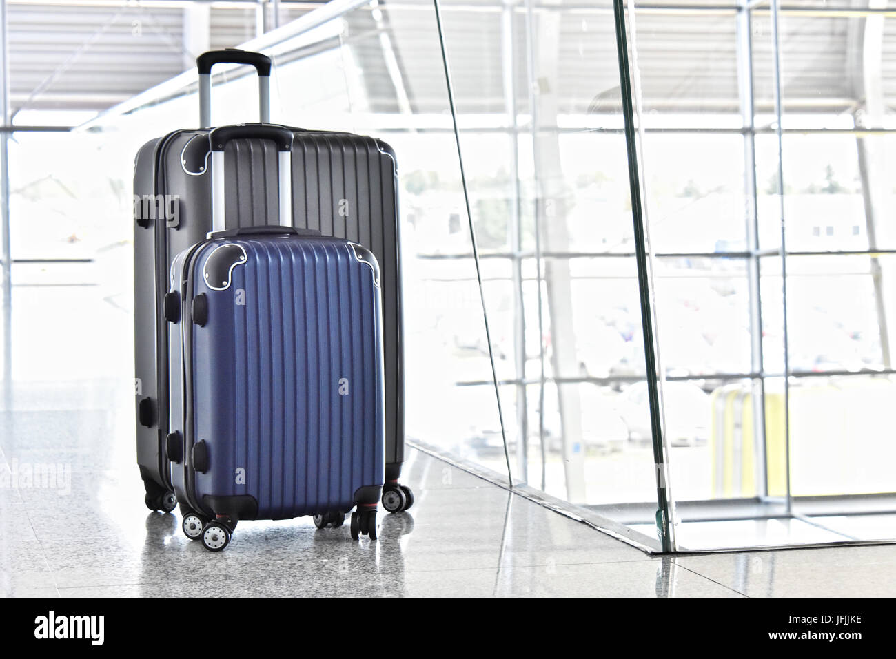 Two plastic travel suitcases in the airport hall. - Stock Image