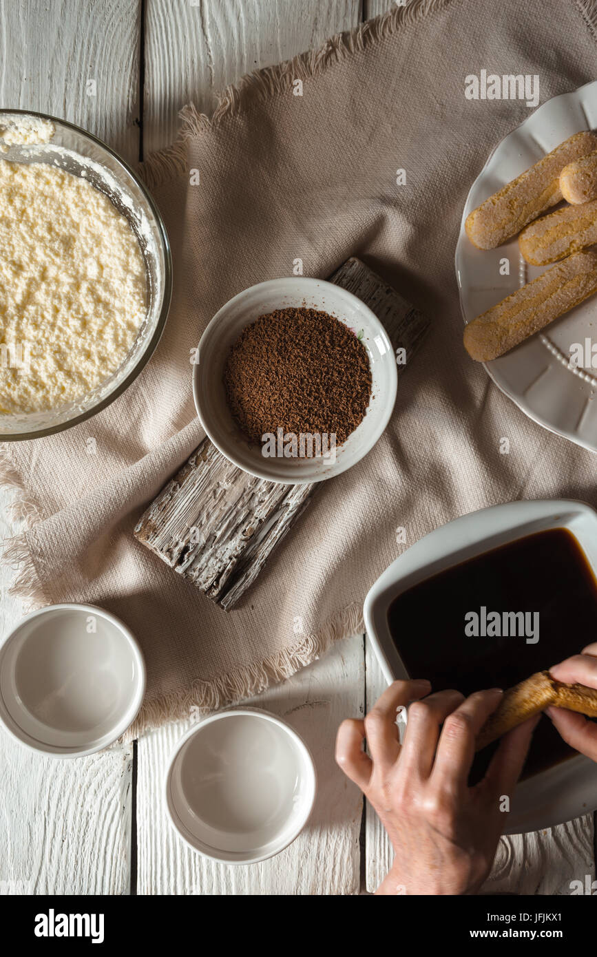 Cooking tiramisu on the white wooden table  top view vertical - Stock Image