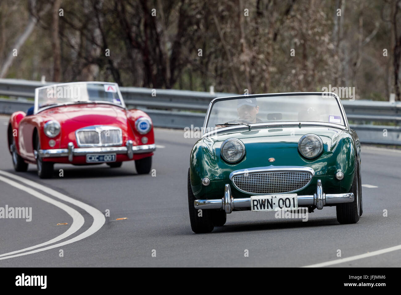 Vintage convertible sports cars driving on country roads near the town of Birdwood, South Australia. - Stock Image