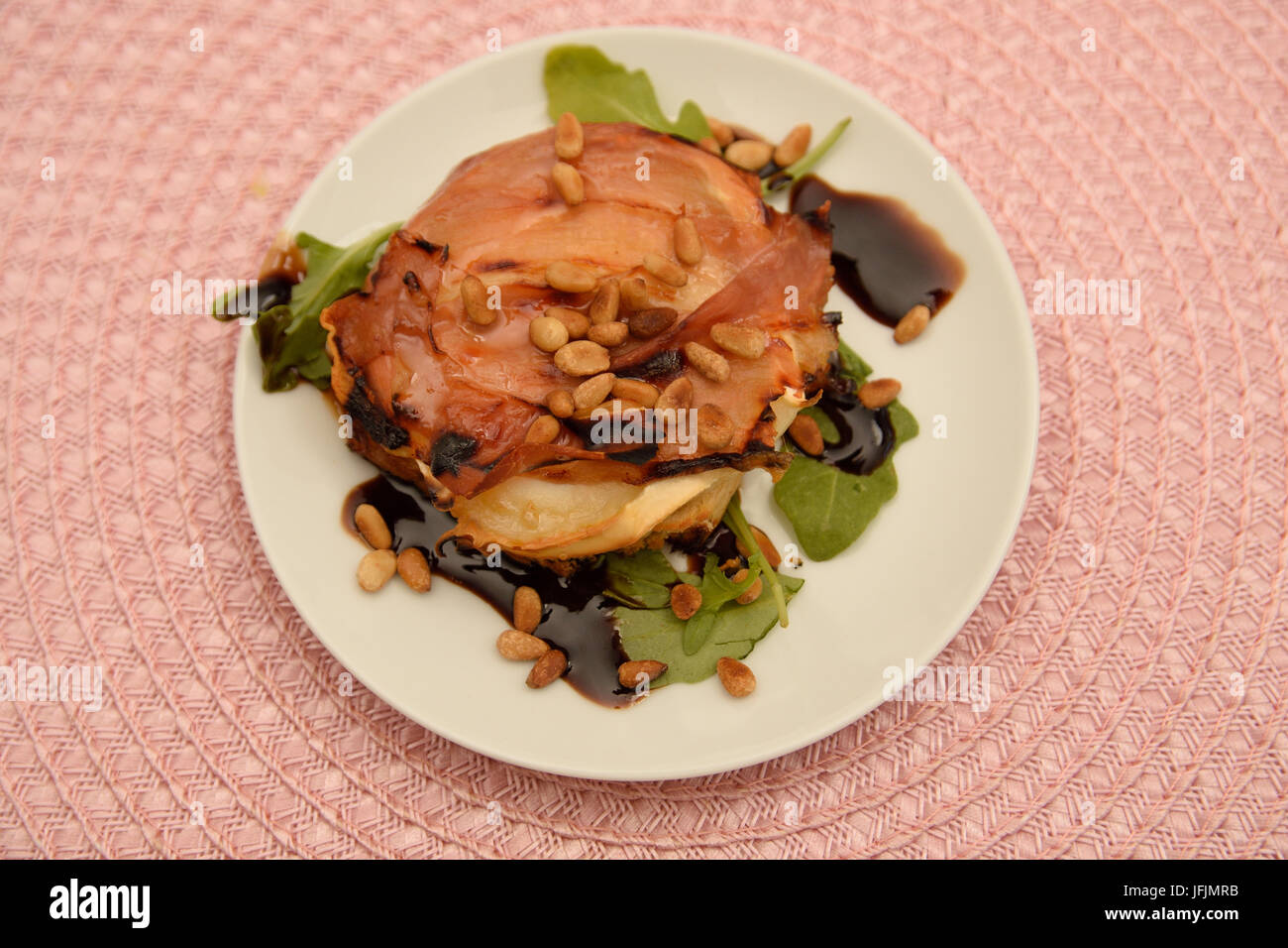 Starter with parma ham and  chevre cheese on a bread with roasted nuts on top and basilica with balsamico vinegar - Stock Image