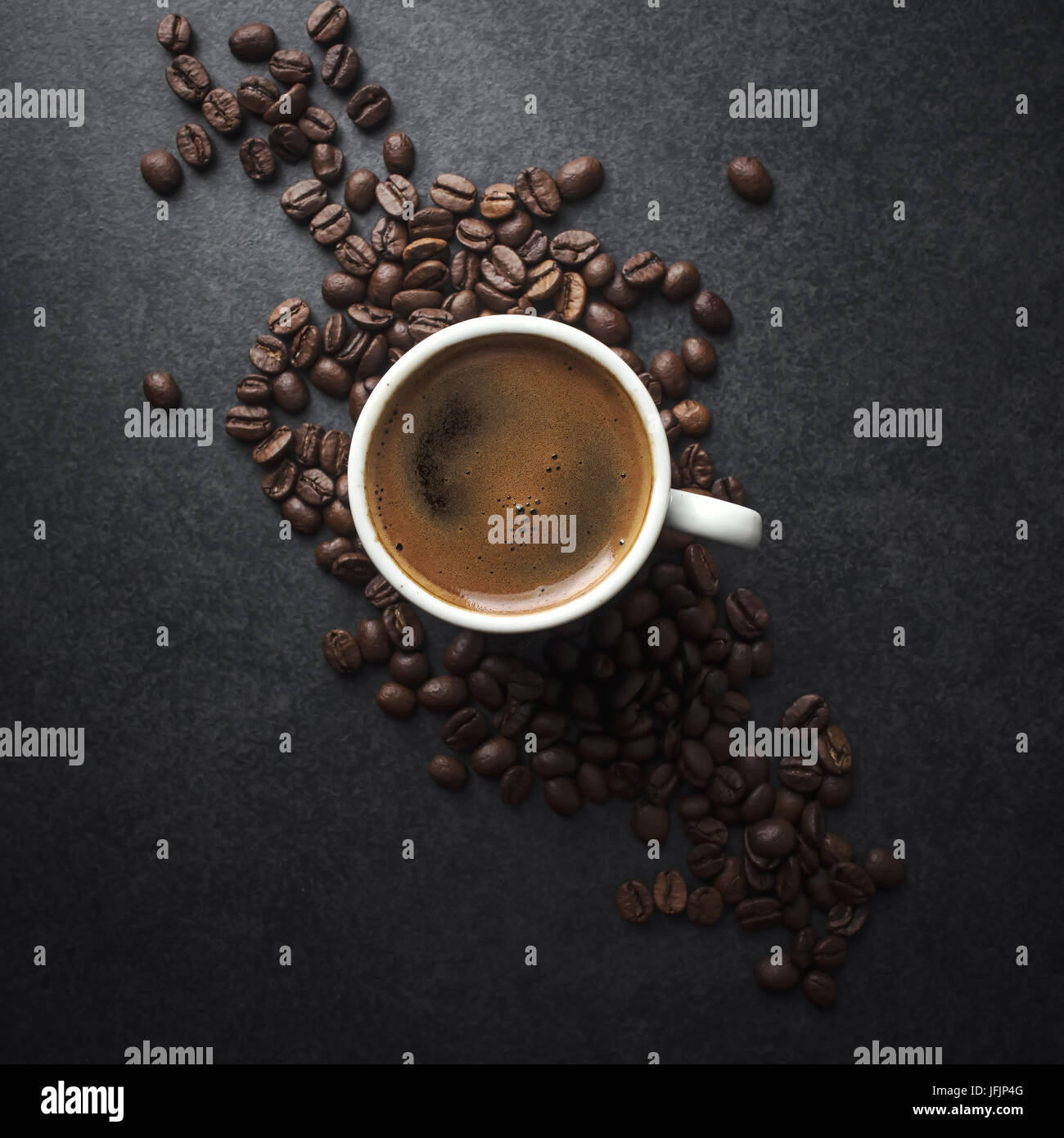 Cup of coffee and beans on table, from above - Stock Image
