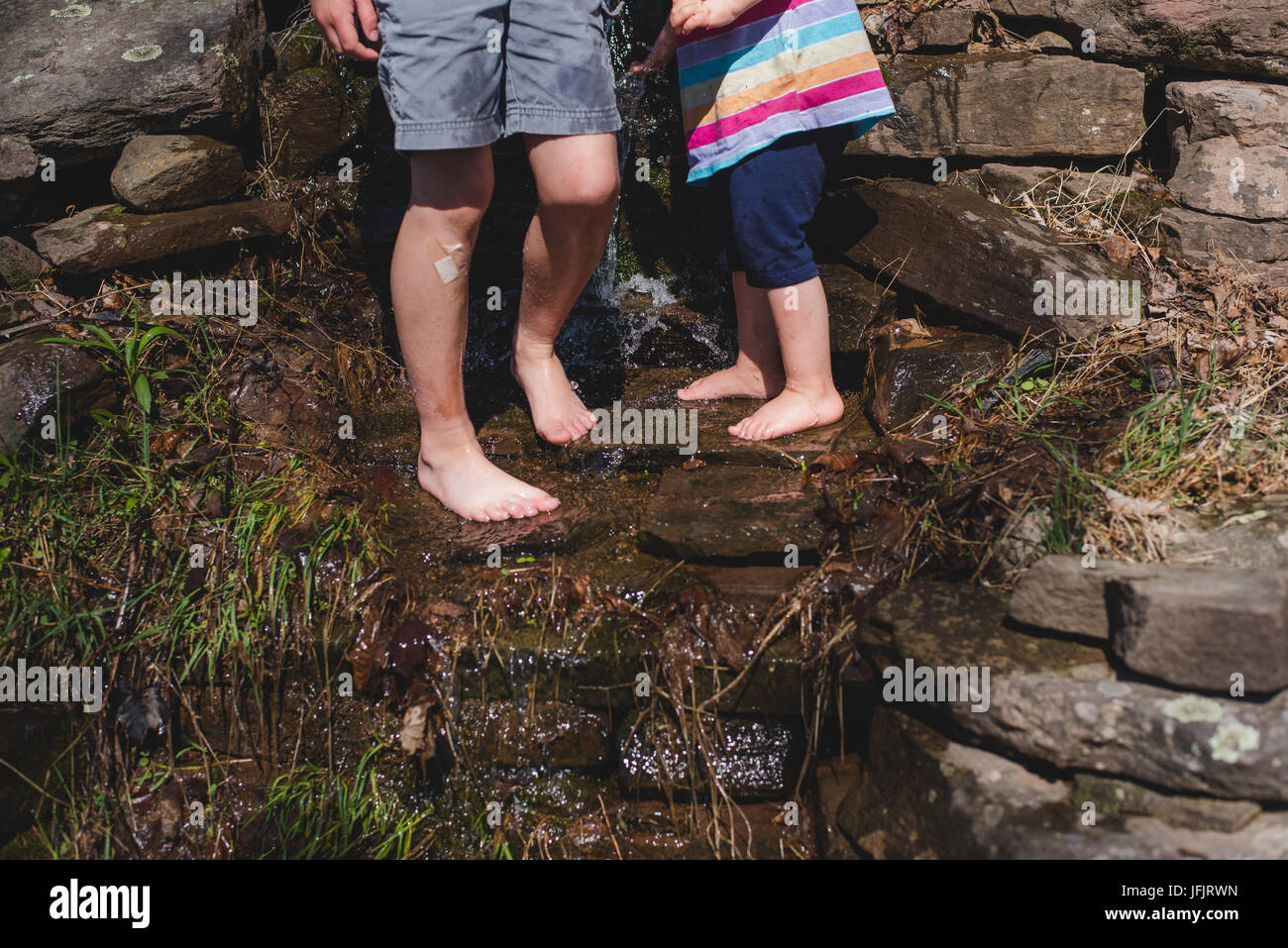 Children play barefoot in a rural area - Stock Image