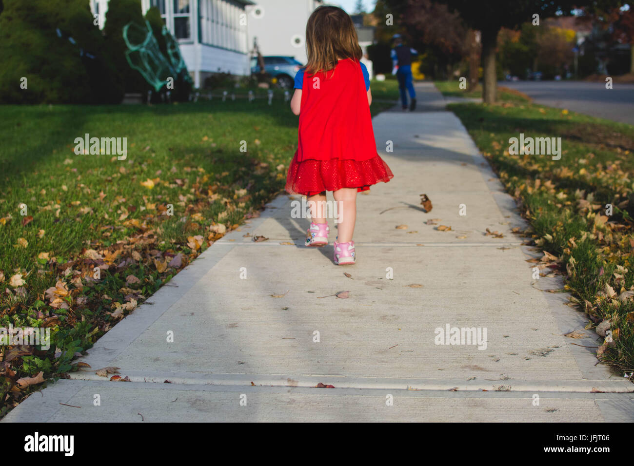 A young girl walks down a sidewalk from behind at sunset in the Fall wearing a red cape. - Stock Image