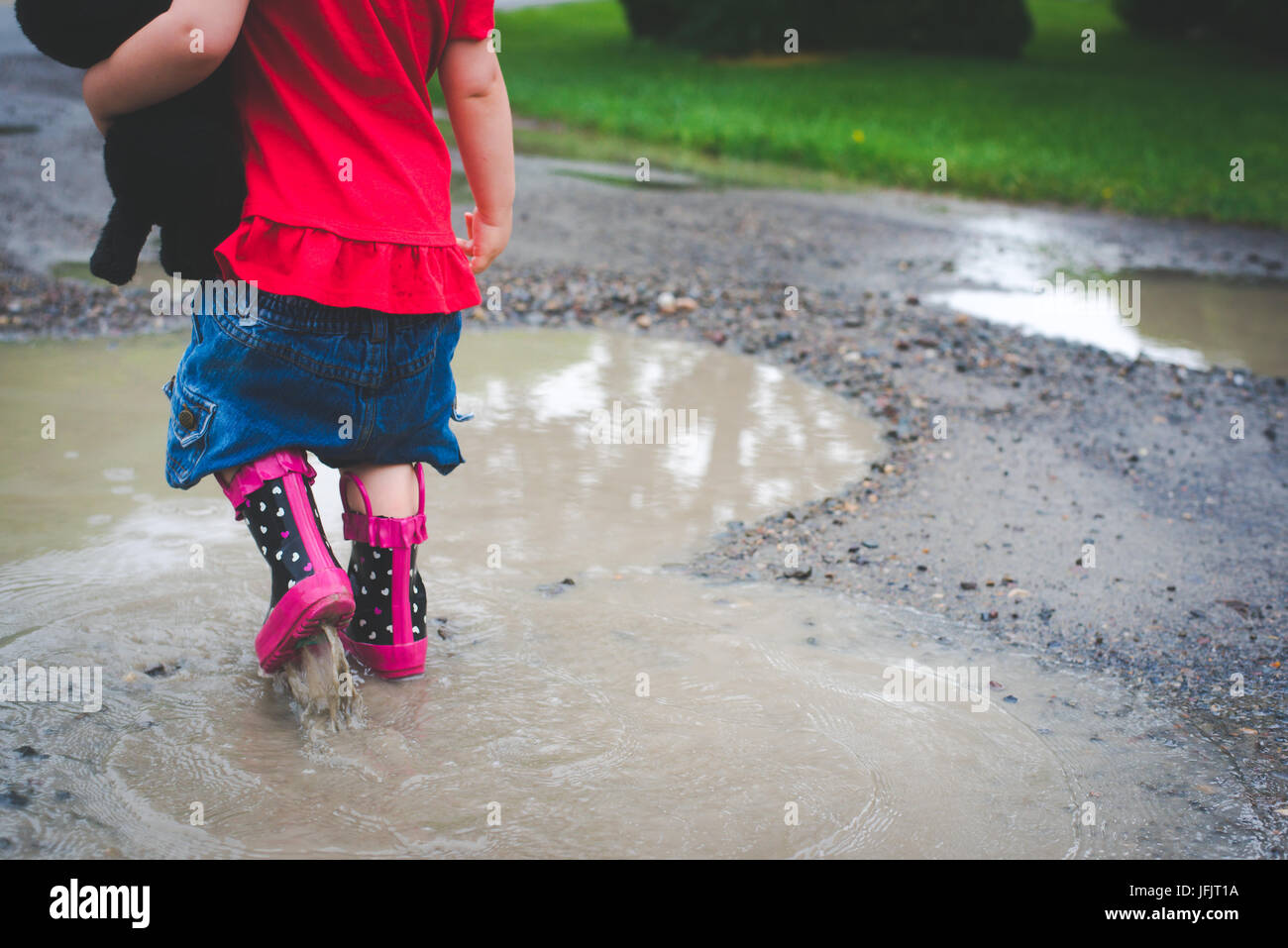 A young girl walks into a mud puddle with rain boots on wearing red and holding a small stuffed dog. Stock Photo