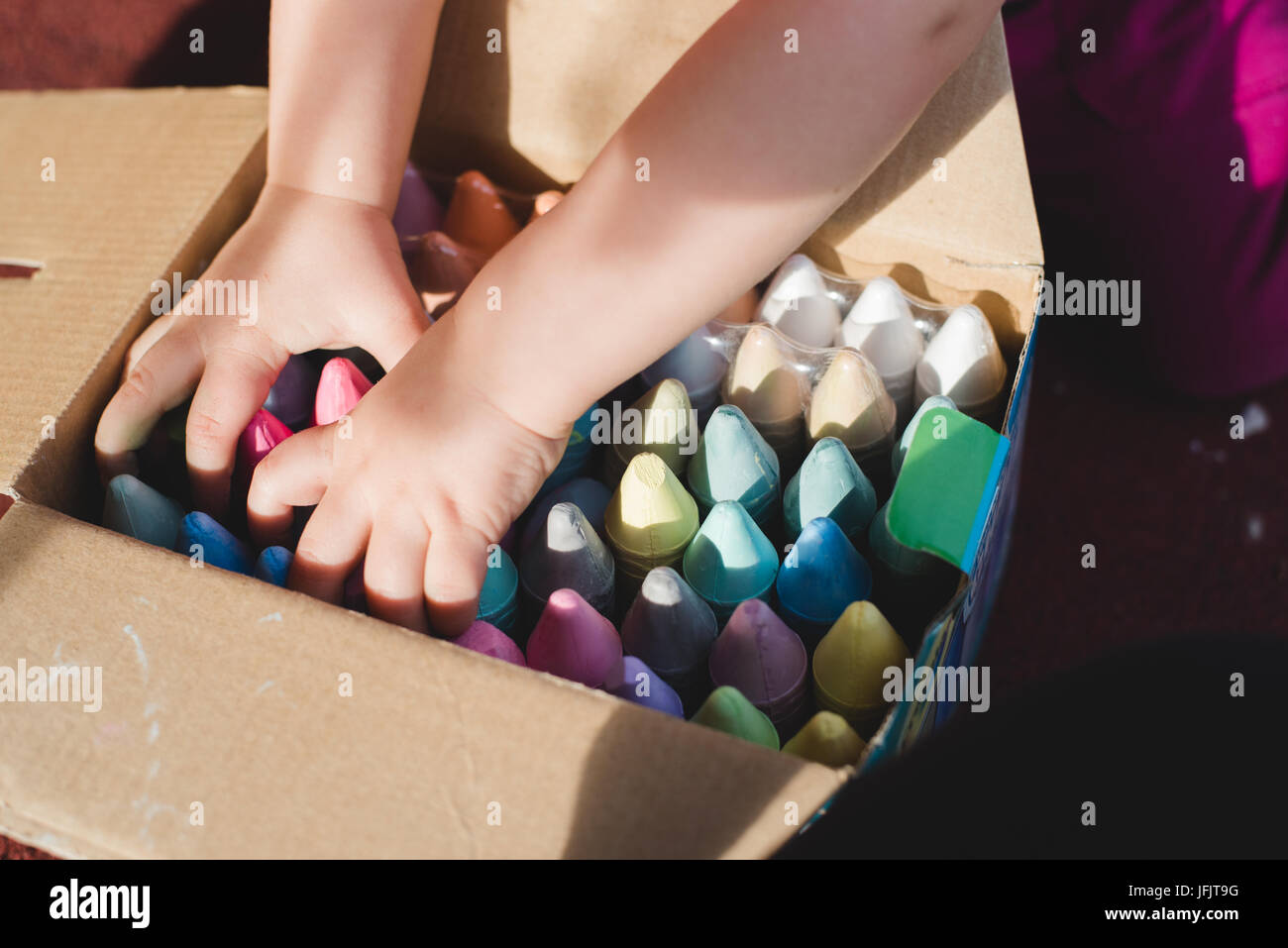 A child's hands reach into a box of sidewalk chalk. - Stock Image