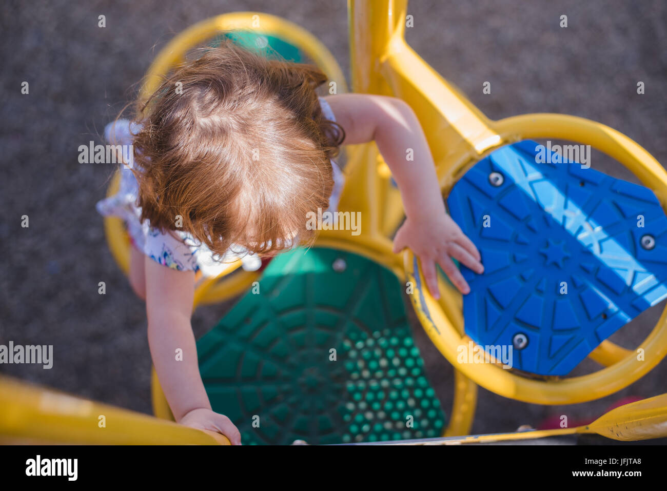 A young girl climbs on playground equipment in the sunlight wearing bright red shoes. - Stock Image
