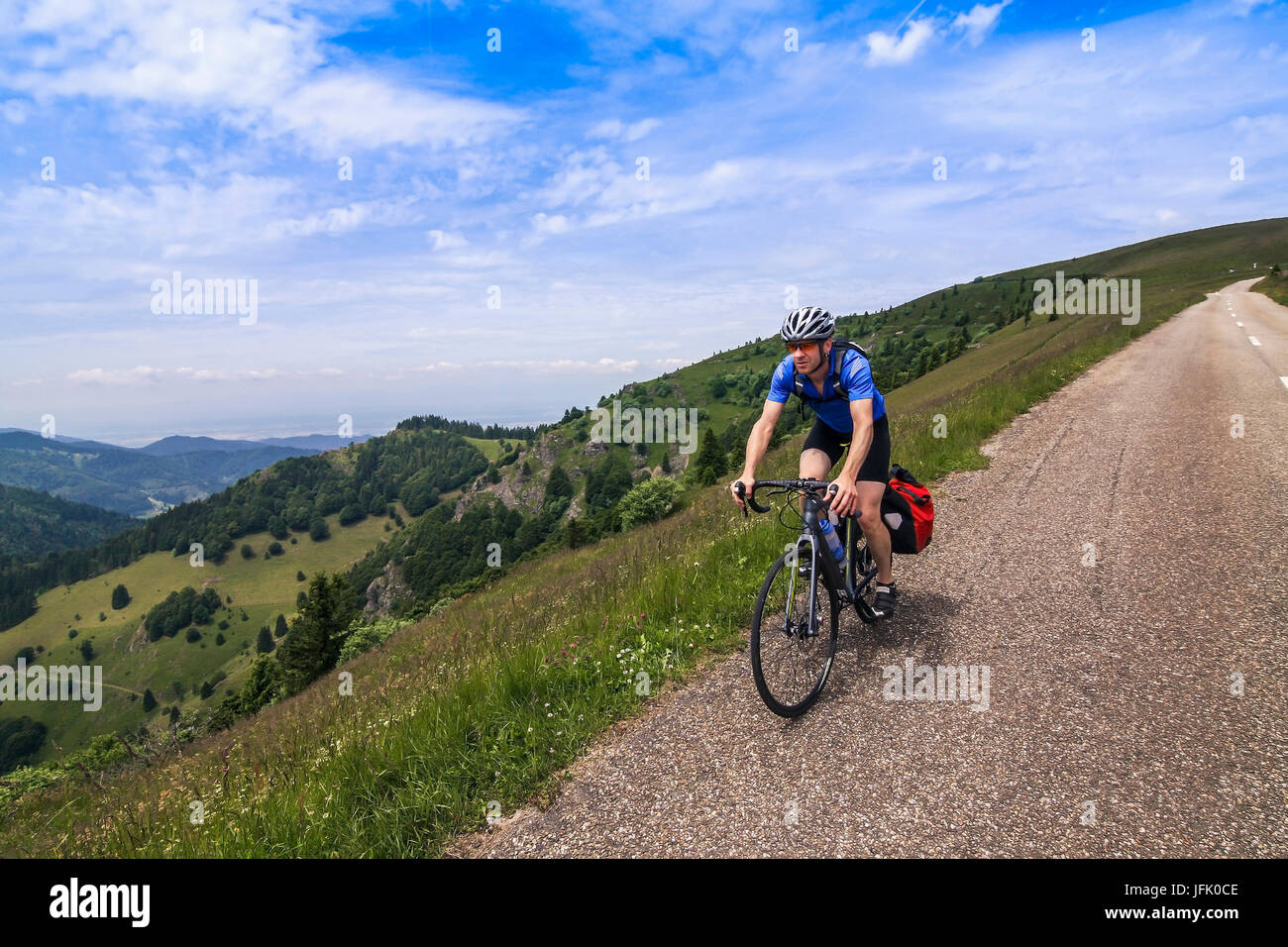 Mature man riding bike on hilly areas - Stock Image