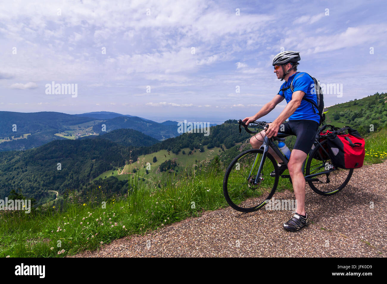 Man sitting on bicycle looking at mountains Stock Photo