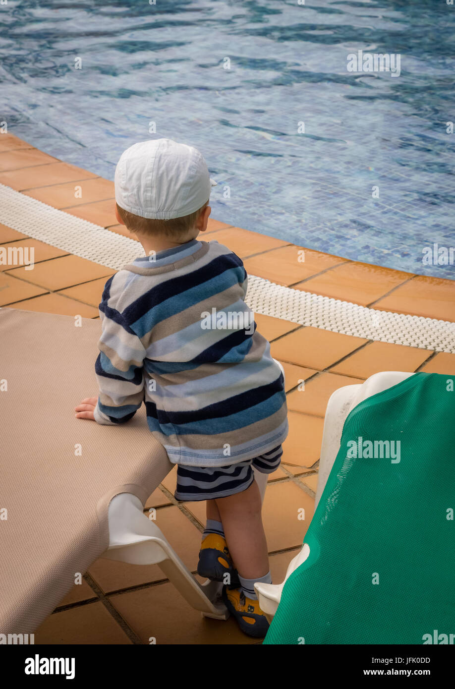 Little boy standing next to the swimming pool Stock Photo
