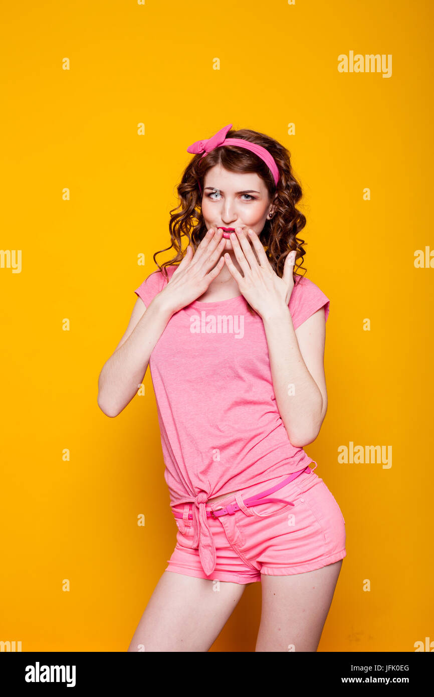 the girl is shy and covers mouth her hands - Stock Image