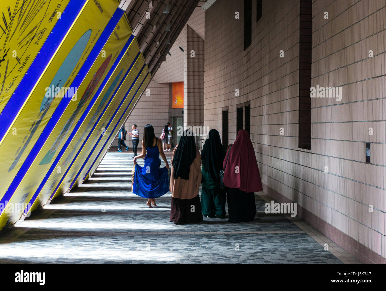 Three female Muslim tourists wearing hijabs (headscarves) in Hong Kong, architecture backdrop angled columns - Stock Image
