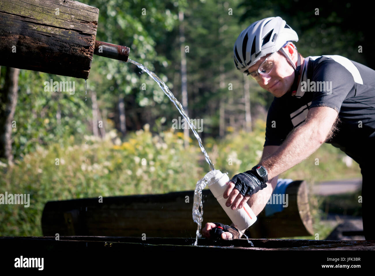 Biker filling water bottle in forest - Stock Image