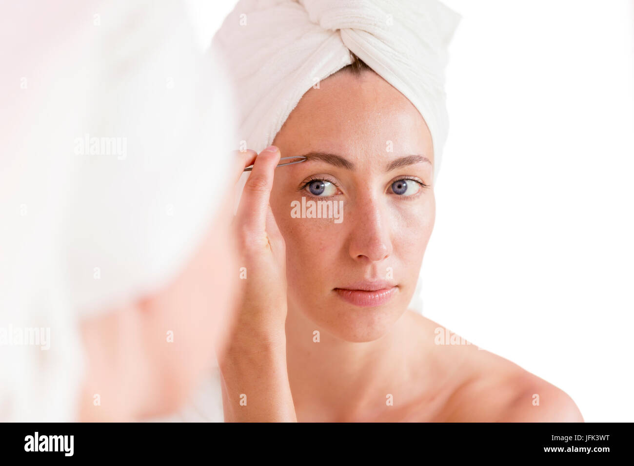 Woman Shaping Of Her Eyebrows With Tweezers Looking In Mirror Stock