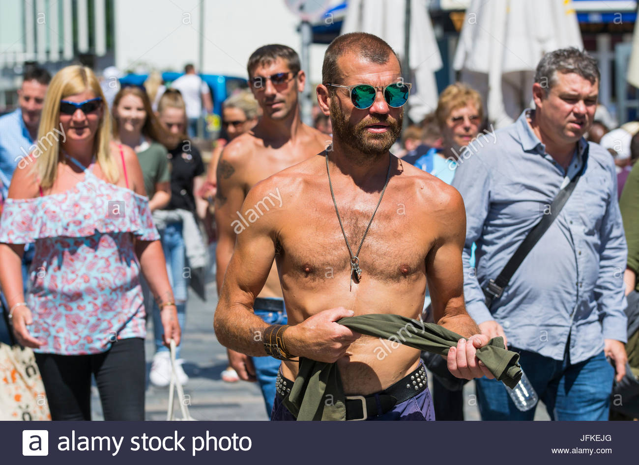 Shirtless muscly man possibly in his 30s wearing sunglasses walking through a busy street on a hot day in Summer - Stock Image