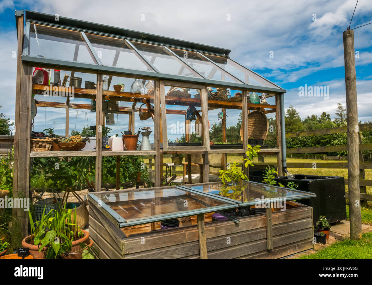 Garden greenhouse and glass covered raised growing bed, sunny Summer ...