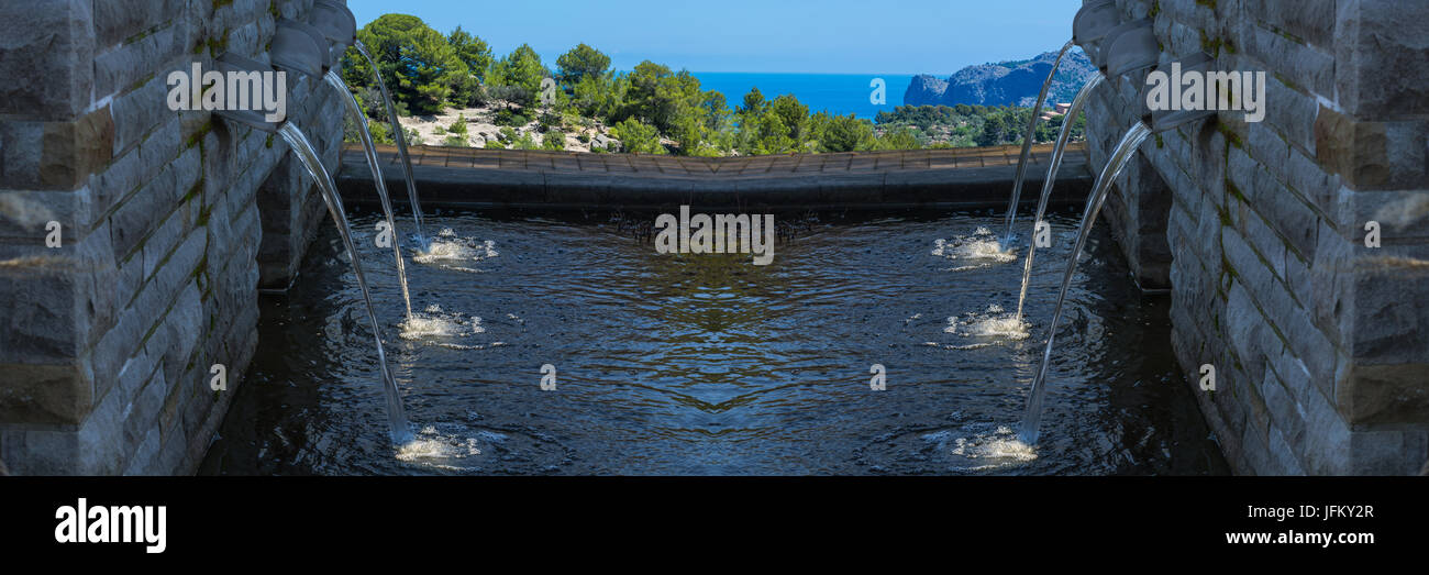 Modern fountain with six spotlighted water drains - Stock Image