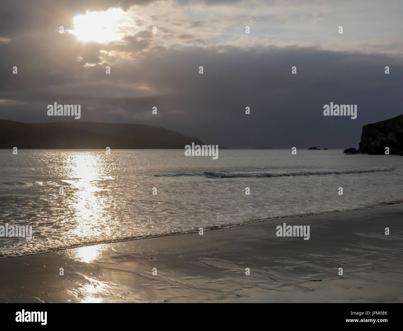 Low sunlight of setting sun reflected on wet sand in remote bay in Northern Scotland near Durness, Sutherland, UK - Stock Image