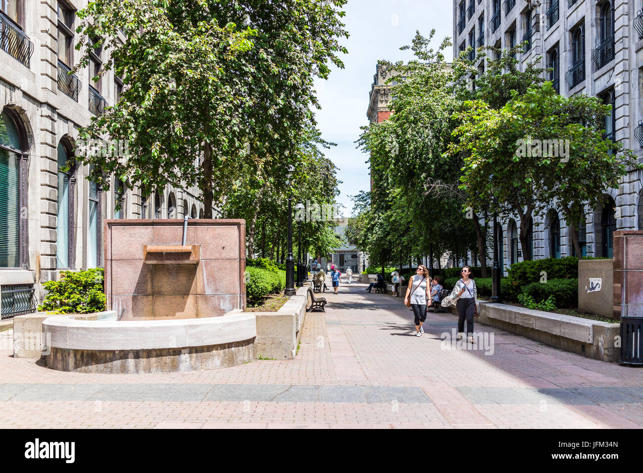 Montreal, Canada - May 28, 2017: Old town area with park on Rue le Royer during summer day with people sitting and - Stock Image