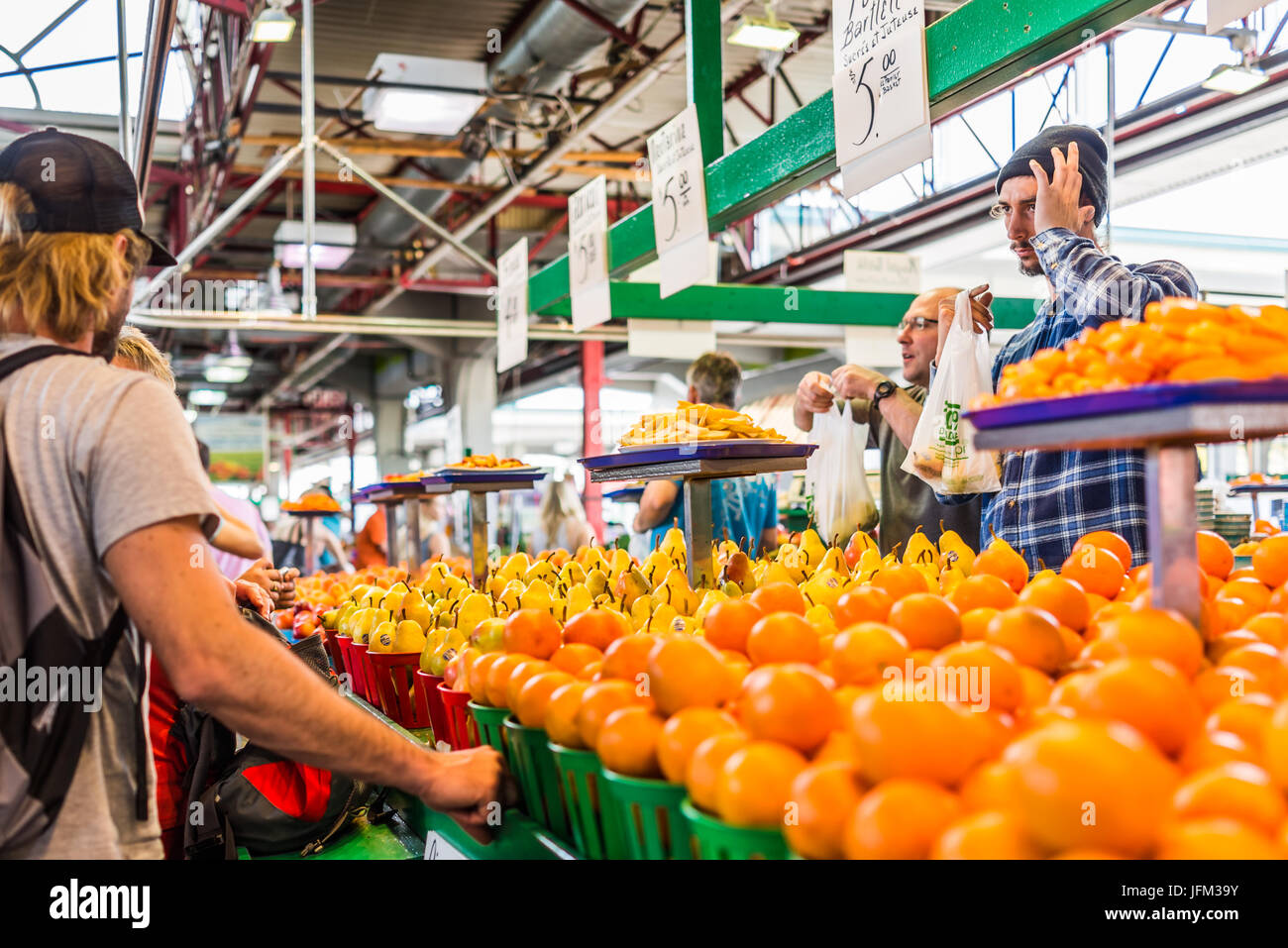 Montreal, Canada - May 28, 2017: Man selling produce by fruit stand with sample slices at Jean-Talon farmers market - Stock Image