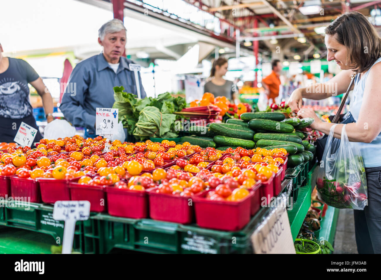 Montreal, Canada - May 28, 2017: Man selling produce by fruit stand with woman buying cucumbers at Jean-Talon farmers - Stock Image