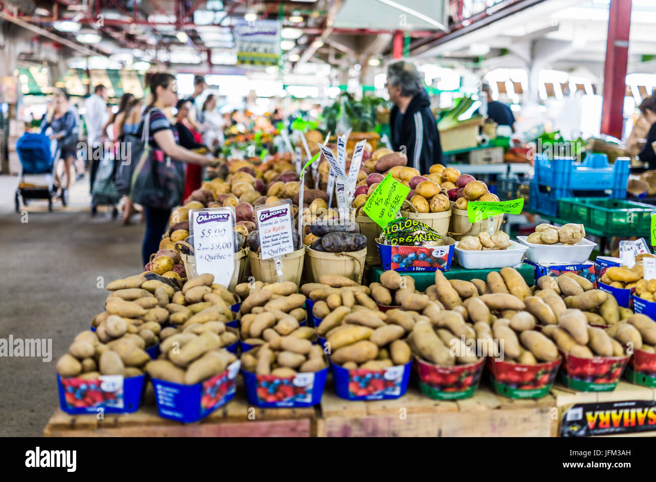 Montreal, Canada - May 28, 2017: Man selling produce by stands at Jean-Talon farmers market with displays - Stock Image