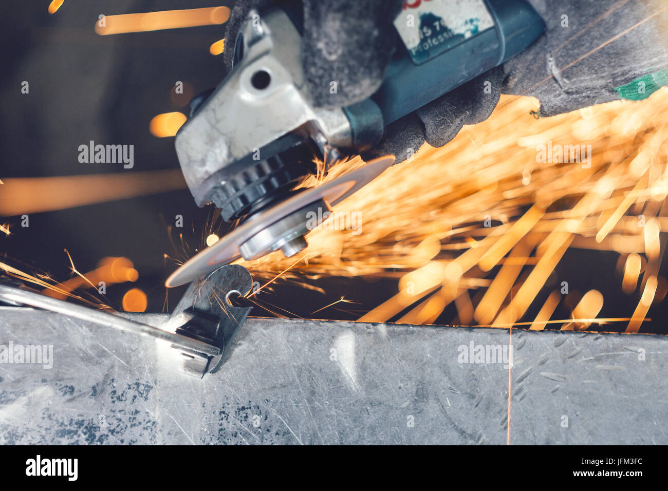 Cutting of curlicue hook using hand angle grinder and spreading sparks all around - Stock Image