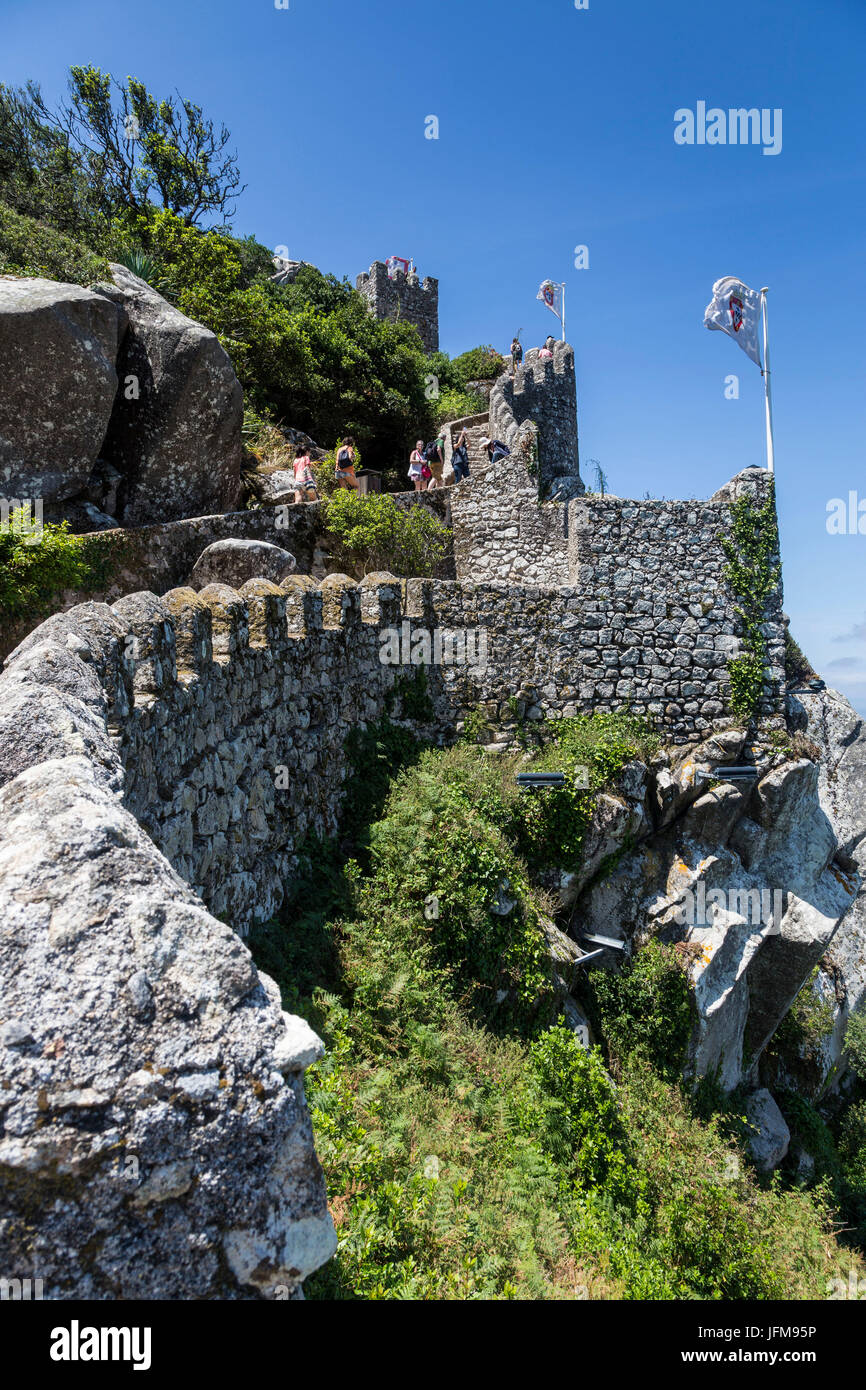 Tourists proceed towards the fortified stone tower of Castelo dos Mouros Sintra municipality Lisbon district Portugal - Stock Image