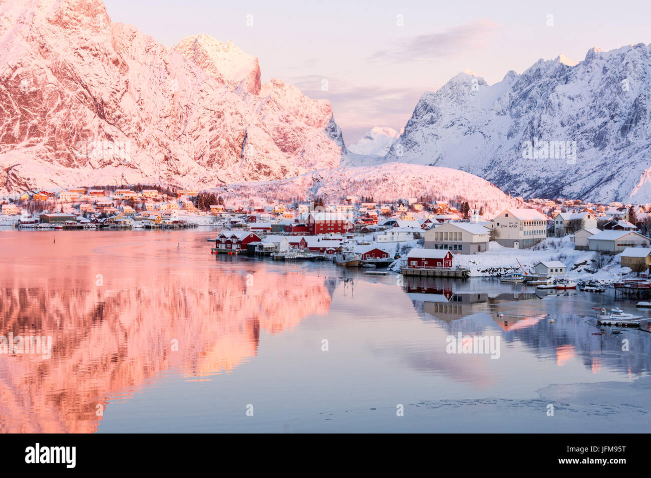 Pink sunrise and snowy peaks frame the frozen sea and the fishing village Reine Bay Nordland Lofoten Islands Norway - Stock Image