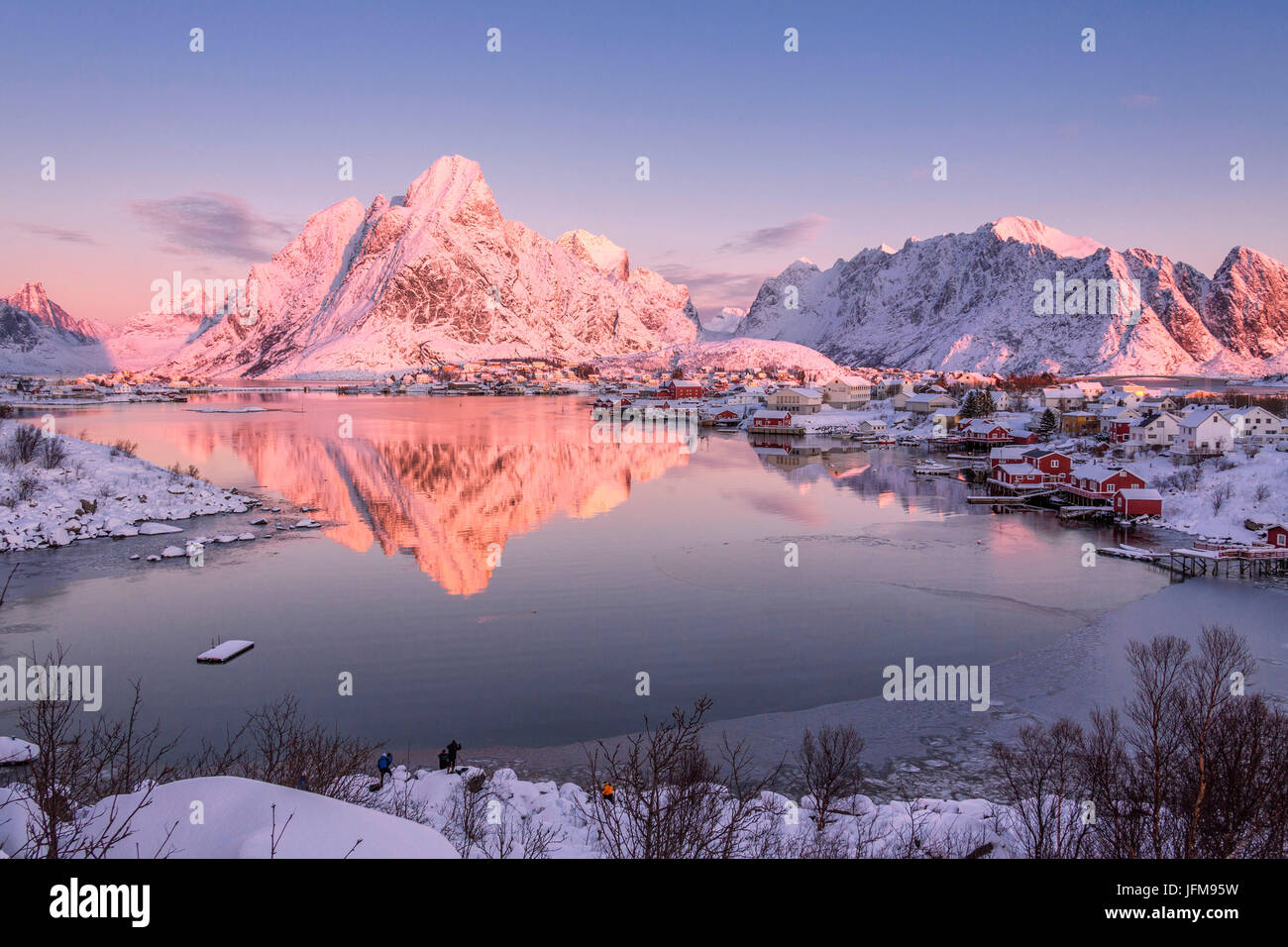 Snowy peaks are reflected in the frozen sea at sunset Reine Bay Nordland Lofoten Islands Norway Europe - Stock Image