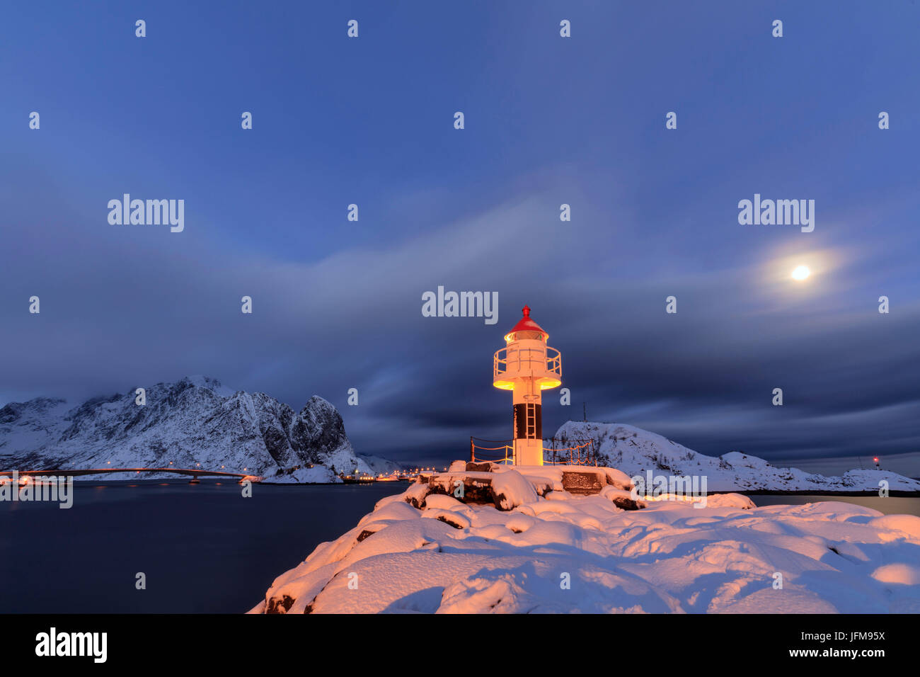 Lighthouse and full moon in the Arctic night with the village of Reine in the background Nordland Lofoten Islands - Stock Image
