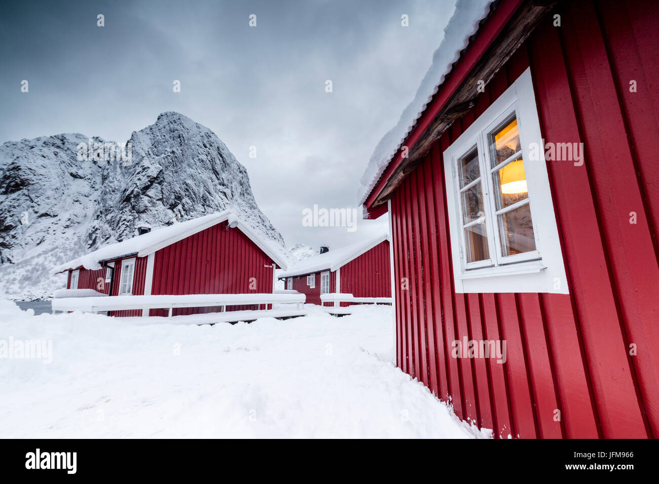Clouds on the typical red houses of fishermen called Rorbu surrounded by snowy Hamnøy Lofoten Islands Northern - Stock Image