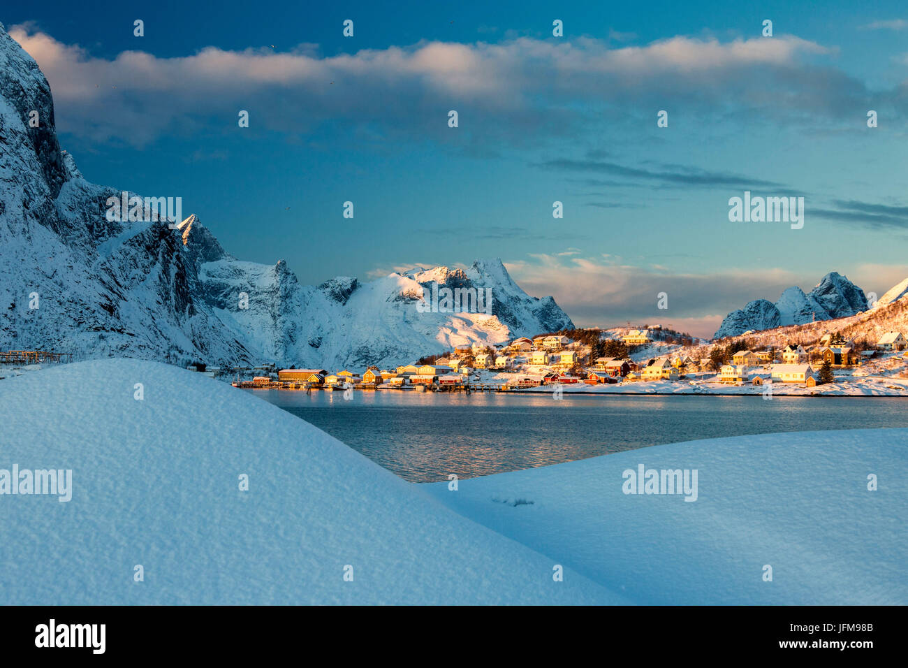The blue color of dusk on the fishing village and the snowy peaks Kvalvika Andøya Reine Nordland Lofoten Islands - Stock Image