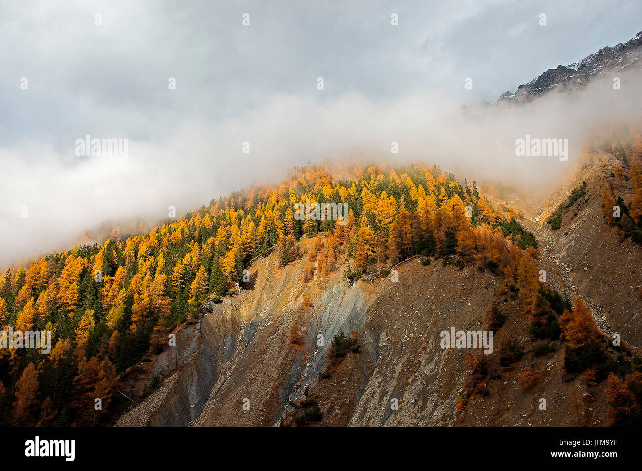 Val Zebru, Bormio, Lombardy, Italy One glimmer of light is the space between the clouds and illuminates the Val - Stock Image