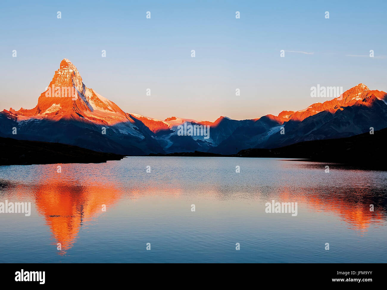 An alpine lake reflecting the Matterhorn and other peaks in the sunrise's colours, Valais, Swiss alps - Stock Image