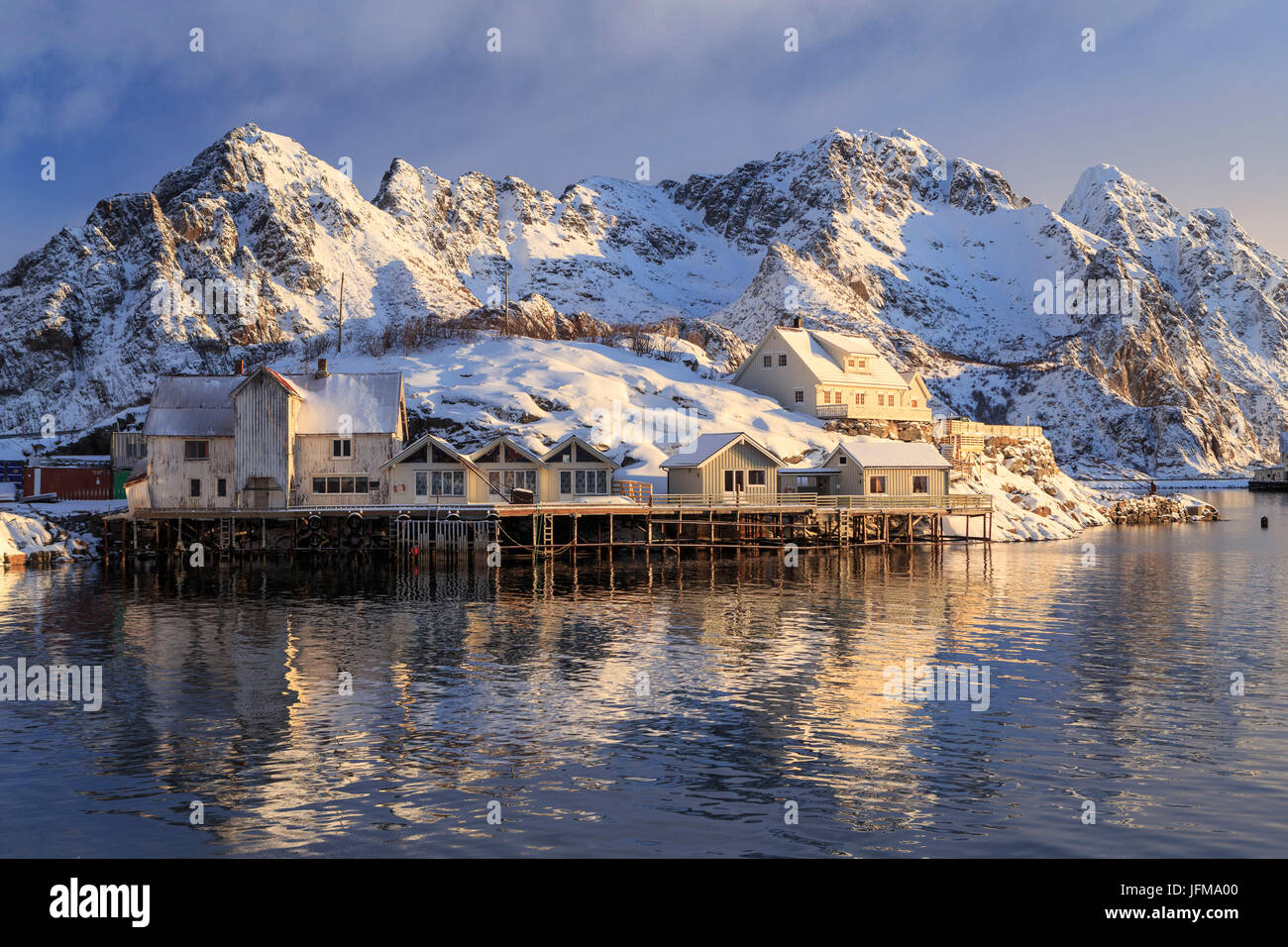 Stilt houses perched over the water in front of the stunning mountains of Henningsvær Fishing village, Lofoten - Stock Image